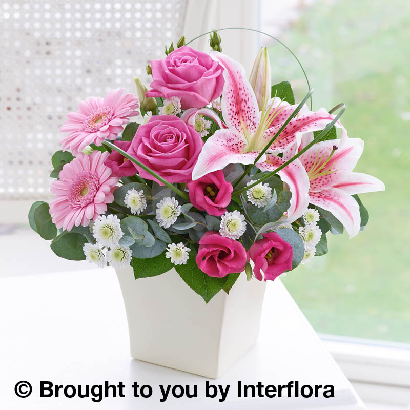 pink arrangement of flowers in a cream pot