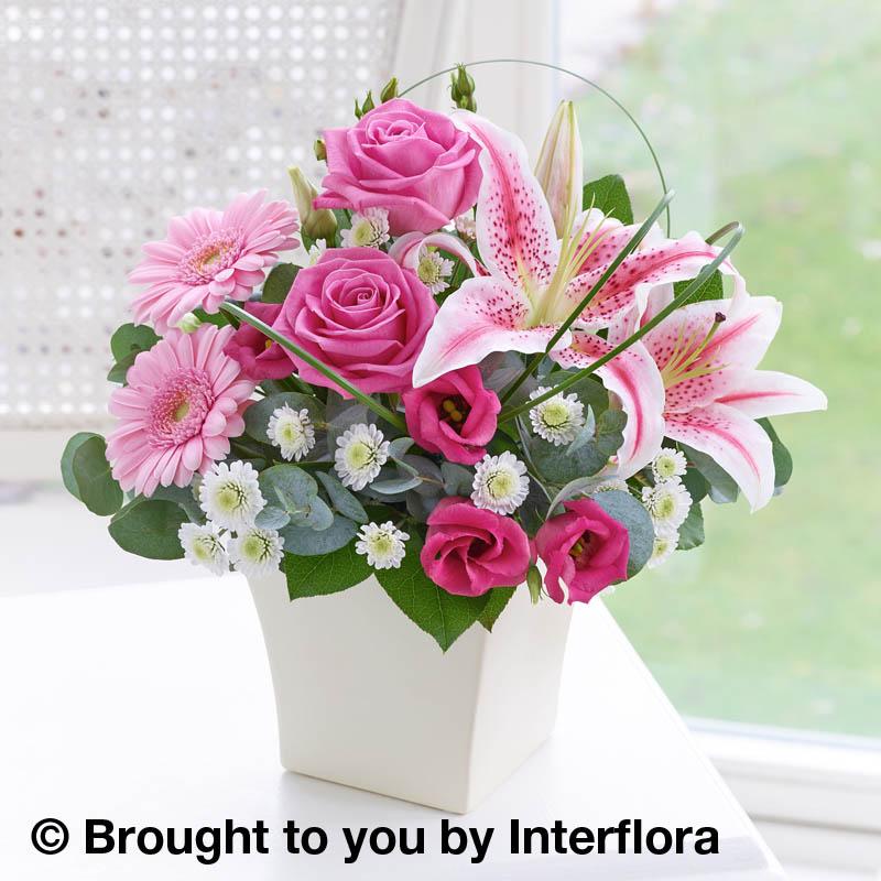 pink arrangement of flowers in a cream pot