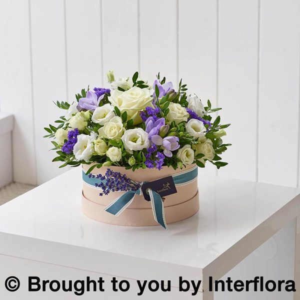 Hatbox with lilac and white fresh flowers